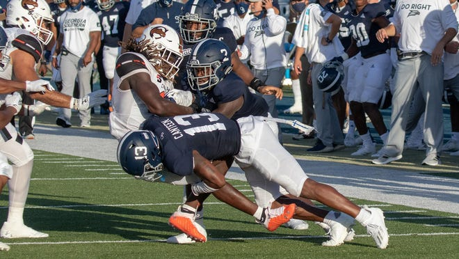 Georgia Southern cornerback Derrick Canteen (13) and safety Javon Jackson (2) tackle a Campbell receiver on Sept. 12 at Paulson Stadium in Statesboro. Georgia Southern won 27-26.