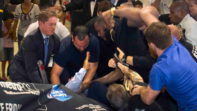 In this Aug. 4, 2014 photo, MGM Grand security try to to separate UFC light heavyweight champion Jon Jones and challenger Daniel Cormier after the two started fighting during a UFC press conference at the MGM Grand in Las Vegas.