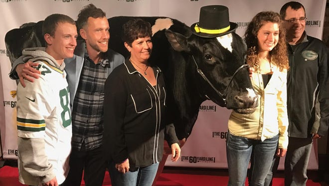 """From left, Jordan Ebert, """"The 60 Yard Line"""" filmmaker Ryan Churchill, Renee Ebert, Whitney Ebert and Randy Ebert pose with 4-year-old Reaction the cow on the red carpet at the movie's world premiere Sunday at the Wisconsin Film Festival in Madison. The cow owned by Ebert Enterprises in Algoma has a role in the Green Bay Packers-themed comedy filmed mostly in Green Bay."""