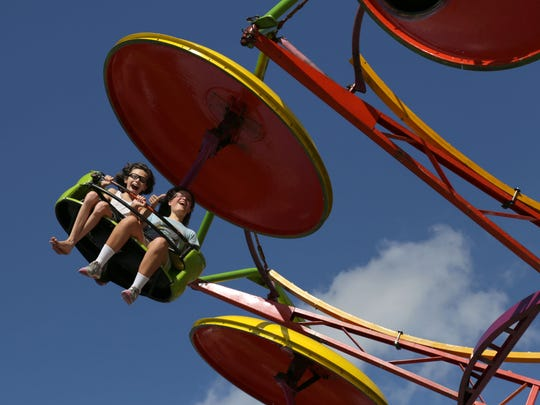 Joshua, 13, and Samantha Martinez, 11, enjoy a carnival ride at the Lexington Blueberry Festival on Thursday. The festival will continue throughout this weekend.