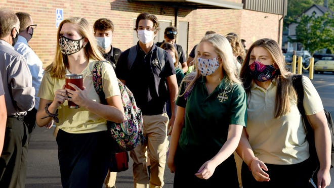 Wearing masks, students arrive to St. Mary Catholic Central High School for their first day of school Aug. 18.