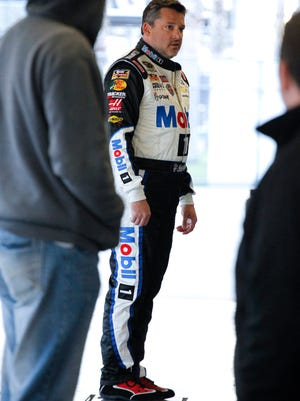 Tony Stewart stands on a scale in the garages after there was an issue with the weight of his car during a practice session for a NASCAR Sprint Cup Series auto race at Daytona International Speedway, Friday, Feb. 13, 2015, in Daytona Beach, Fla. (AP Photo/Terry Renna)
