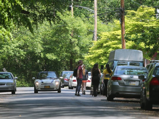 University of Delaware students travel up and down White Clay Drive in search of an American black bear that was spotted in the area Thursday.