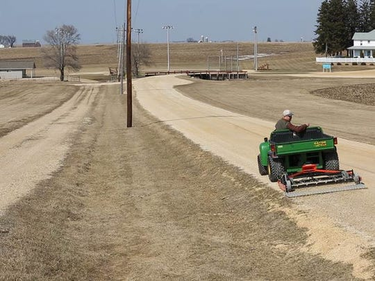 "Former ""Field of Dreams"" owner Don Lansing still works daily at the farm where he was born. Here he drives his John Deere down one of two driveways that leads from the road to the field, a visible remnant from when Lansing and his neighbors shared ownership of the field and feuded over how to market it."