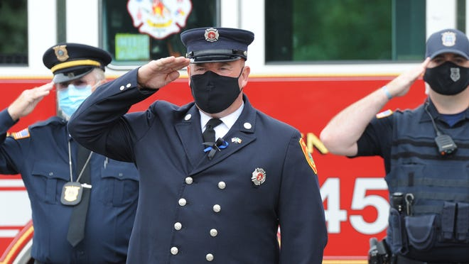 """Firefighter Kevin Enright salutes the raising of the flag during a ceremony to mark the anniversary of the 9/11 terrorist attacks. The event was held Friday at Yarmouth Fire Department Station 3. Despite the pandemic, department members were """"very passionate"""" about continuing the tradition of honoring fallen colleagues, Fire Chief Philip Simonian said."""