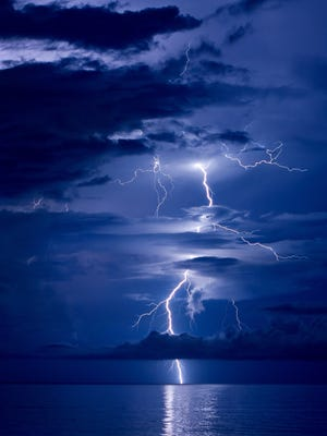 Lightning strikes over the ocean in this file photo taken Aug. 16, 2011, near Vero Beach. A woman died and another man was hospitalized after being struck by lightning Wednesday, May 16, 2018, in Parkland.