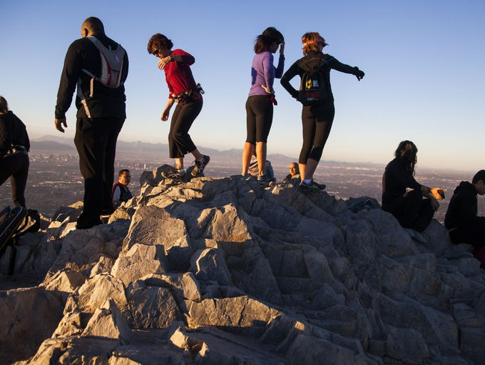 Hikers sit at the top of Piestewa Peak on Sunday, January