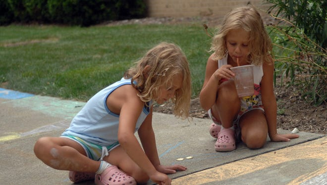Six-year-olds in Wayne drawing with chalk on the sidewalk.