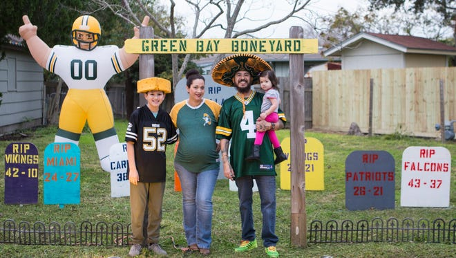 The Flores family Ethan (from left) , Natalie Marcos and Zoe stand in the entrance way of the The Green Bay Boneyard on their front lawn in Corpus Christi. Marcos creates a tombstone for every team the Green Bay Packers defeat this season and sticks it inside the boneyard.