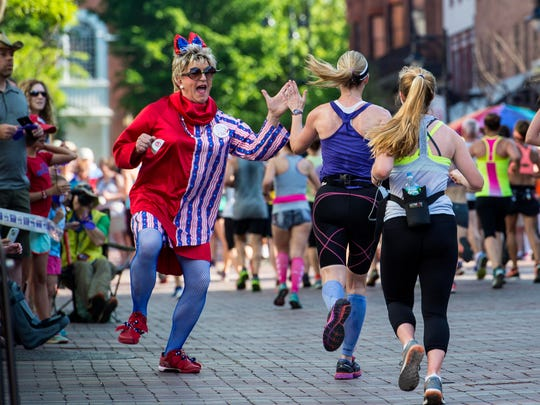 Amber LeMay of the House of LeMay high-fives a runner on Church Street during the People's United Bank Vermont City Marathon in Burlington on Sunday, May 29, 2016.