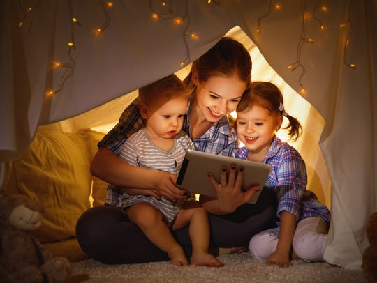 Happy family mother and children playing in tablet