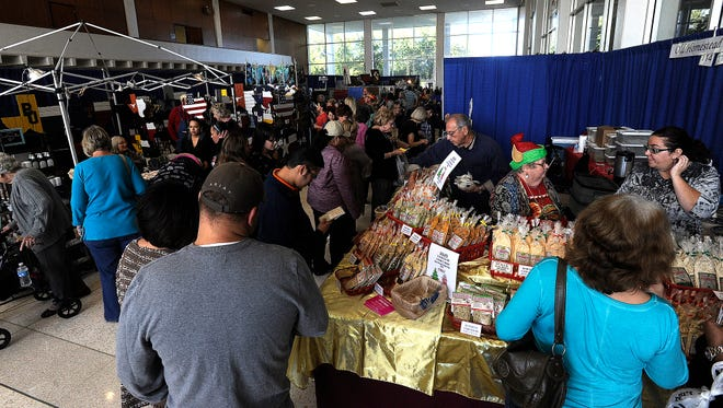 People wait in line for samples from the Old Homestead Gourmet booth during Christmas in November on Saturday, Nov. 12, 2016, at the Abilene Civic Center.