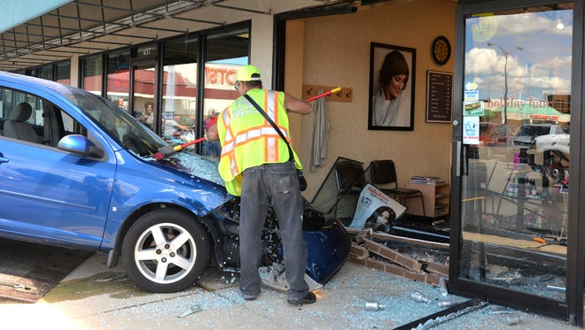 A fire police officer from the Annville-Cleona Fire District sweeps debris off the windshield of a car that drove through the window of Holiday Hair, 455 W. Penn Ave., Cleona on Friday, Sept. 2, 2016. No one was injured. Police said the car was driven by Doris Horn, 85, of Annville.