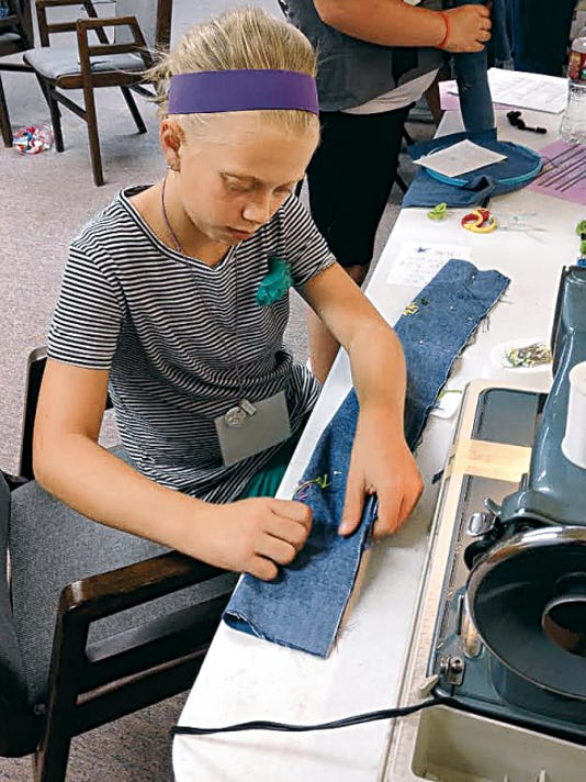 Katie Riesberg sews and embroiders a neck pillow for Hospice patients. Twenty-three neck and back wraps were made during Grace United Methodist Church's Kids With A Mission summer program and 10 have been delivered to Ruidoso's Hospice.