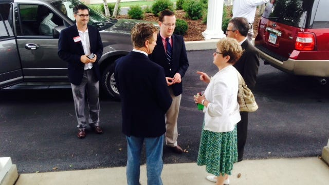 U.S. Sen. Rand Paul, with his back to the camera, speaks to a woman outside a fundraiser in Iowa City today as three of his political advisers listen.
