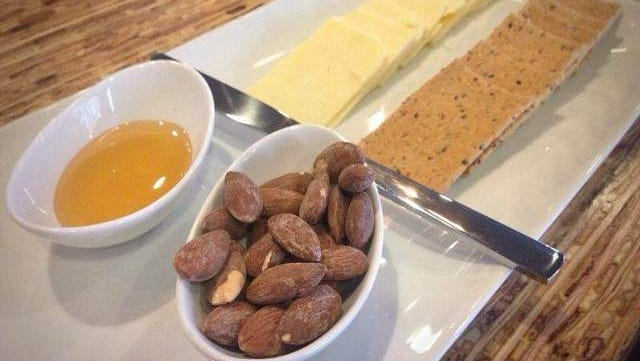 The cheese plate ($4.50), with Milton Creamery Prairie Breeze cheddar, herby crackers, honey, and warm almonds, at Waterstreet Coffee Bar in Coralville.