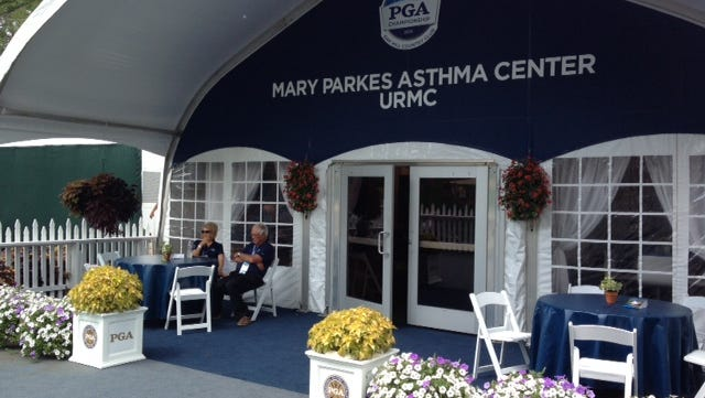 Walt and Barb Parkes in front the the Mary Parks Asthma Center Chalet at the PGA