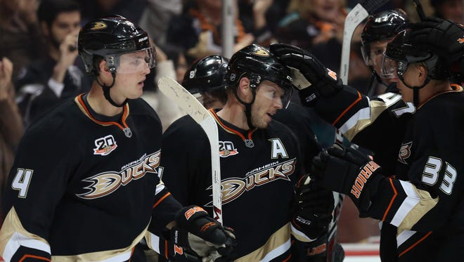 Saku Koivu (second from left) #11 of the Anaheim Ducks celebrates his game winning goal in overtime with Cam Fowler (L) #4 and Jakob Silfverberg (R) #33 against the Phoenix Coyotes at Honda Center on December 28, 2013 in Anaheim, California.