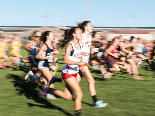 Runners compete during the girls' race at the YAIAA