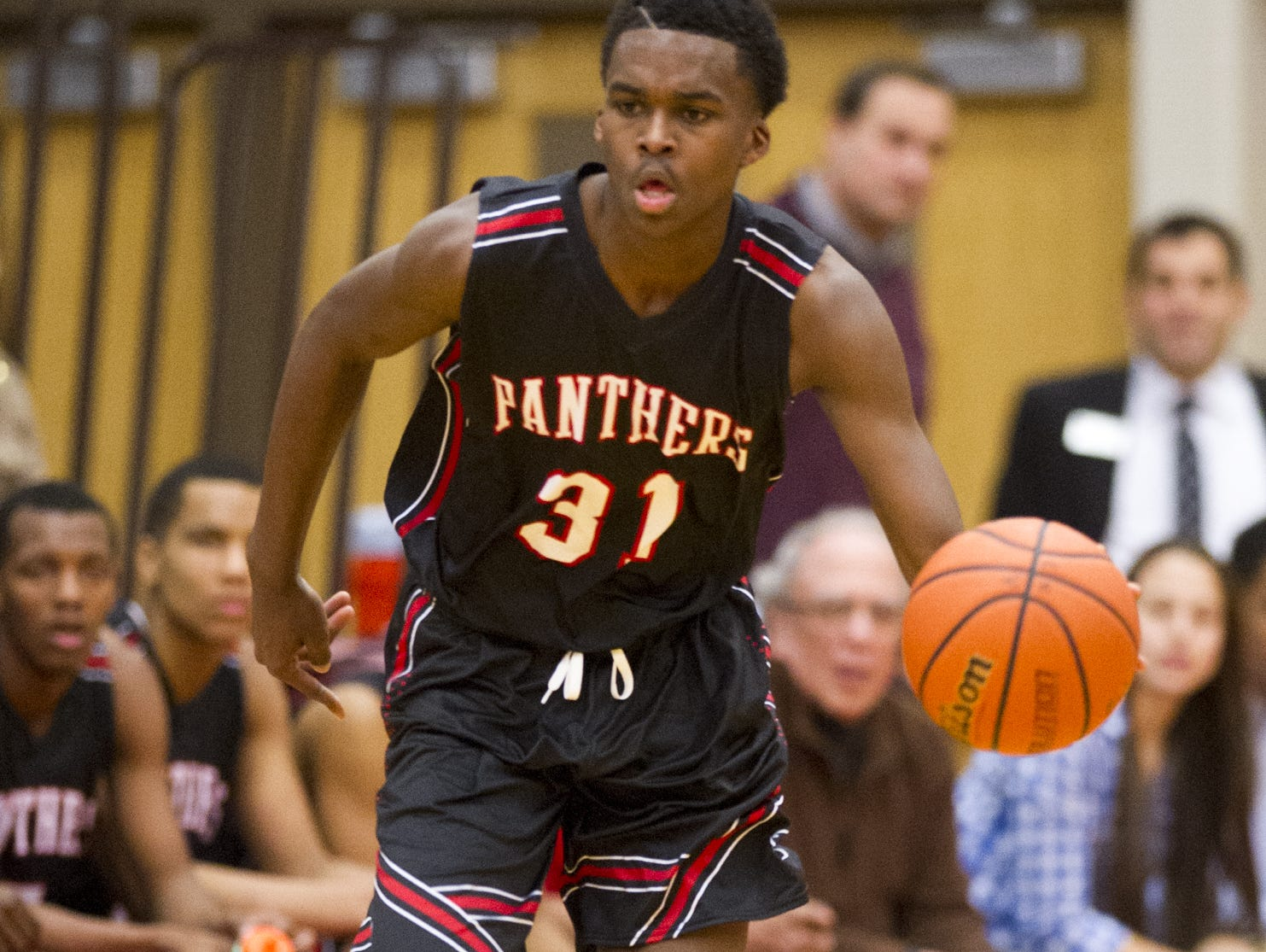 North Central High School sophomore Kris Wilkes (31) brings the ball up court during the first half of action. Lawrence North High School hosted North Central High School in a first-round game of the 2015 Marion County Boys Basketball Tournament, Tuesday, Jan. 13, 2015.