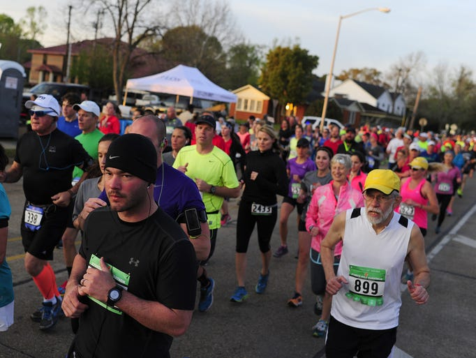 A pack of runners passes the first mile marker near