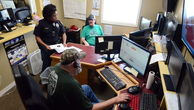 Officer Megan Rue speaks with Jeff Clayton, top, and Randy Sullivan in the Hattiesburg Dispatch Center located across from the Hattiesburg Police Department.