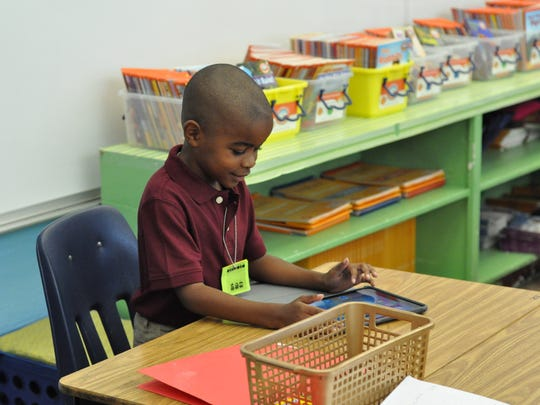 W.O. Hall second-grader Jeremiah Noel explores his new iPad in class Friday morning.