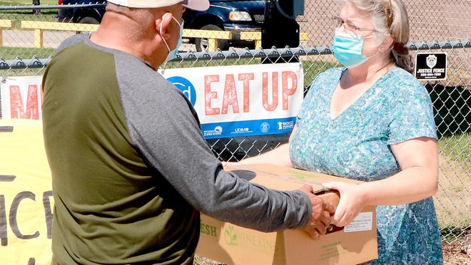 """Patti Miller, food service director at Sturgis Public Schools, hands out a box of produce Friday to a client outside Eastwood Elementary School. Each box of produce weighed 25 pounds and was filled with items such as cabbage, tomatoes and cucumbers.It was the final """"Farmers to Families"""" event of the season. About 1,200 boxes of food were provided during the 2020 campaign."""
