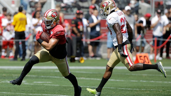 San Francisco 49ers' Trent Taylor, left, catches a pass against Will Redmond during an NFL football training camp in Santa Clara, Calif., Saturday, Aug. 5, 2017. (AP Photo/Jeff Chiu)