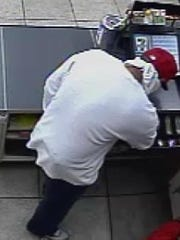 A man reaches into a cash register during one of two