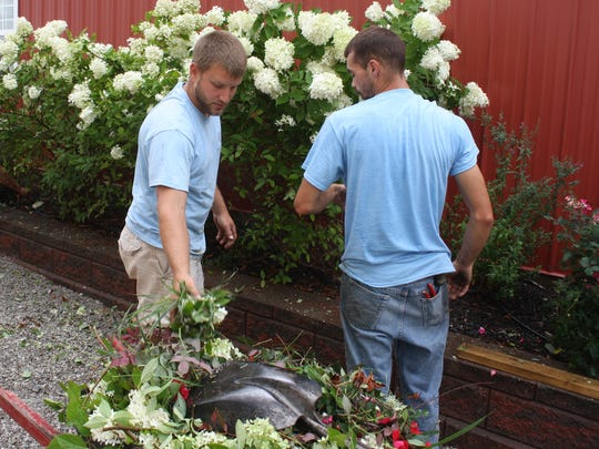 Jacob Kremer, left, and Rob Donaldson, employees of Smith & Jolly Landscape Design in Alexandria, weed and spruce up the flower beds at the Alexandria Fairgrounds Friday, Aug. 22.