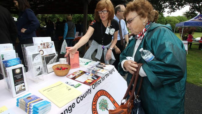 Erinn Braun, left, offers information during an Orange County Senior Health and Fitness Day at Thomas Bull Memorial Park.