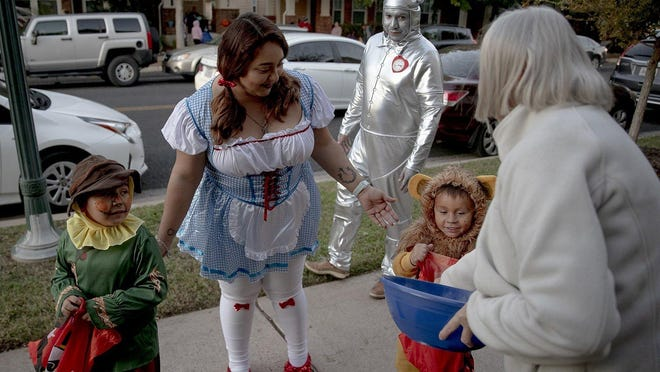 "The Sanchez family, dressed as characters from the ""The Wizard of Oz,"" trick-or-treats last year. This year, pediatricians, infectious disease specialists and the Centers for Disease Control and Prevention are warning against traditional trick-or-treating."