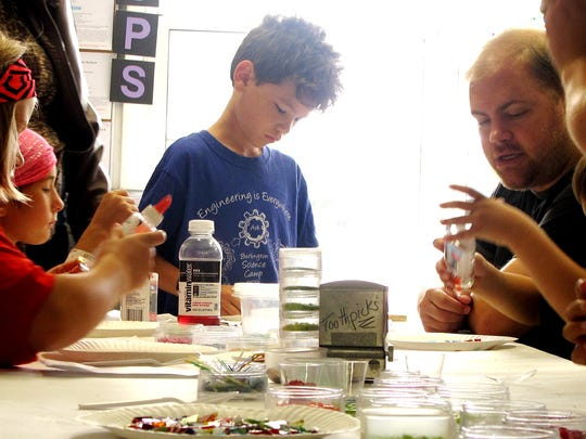 "Nine-year-old Quinn Shelley, center, prepares a ""sun-catcher"" glass sculpture Saturday morning at Davis Studio as a part of the South End Art Hop."