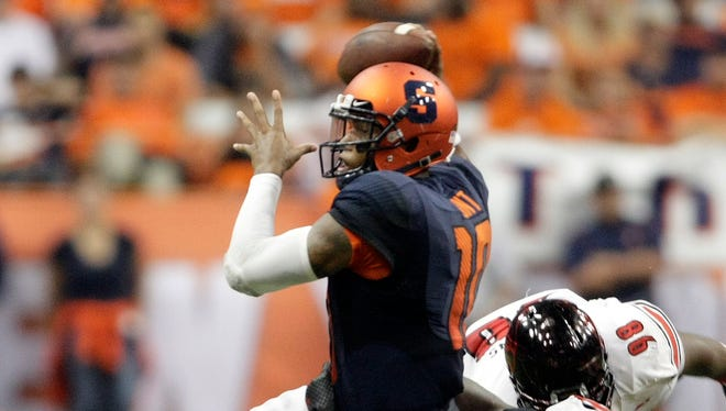Syracuse'?s Terrel Hunt, left, throws a pass while under pressure from Louisville'?s DeAngelo Brown, top right, and Lorenzo Mauldin, bottom right, in the third quarter of an NCAA college football game in Syracuse, N.Y., Friday, Oct. 3, 2014. Louisville won 28-6. (AP Photo/Nick Lisi)