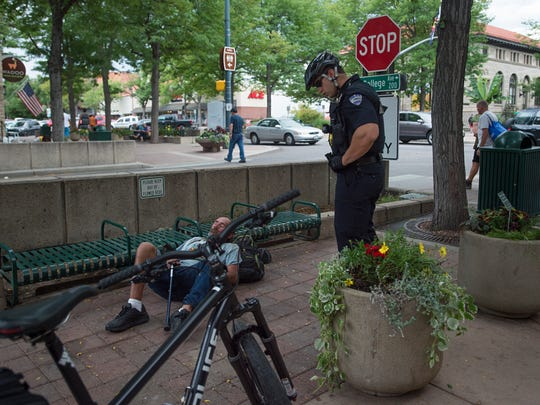 Fort Collins Police Services Officer Matt Hahn speaks to a man who was sleeping near benches during his patrol of Old Town Wednesday as part of the department's increased bike patrols in the area.