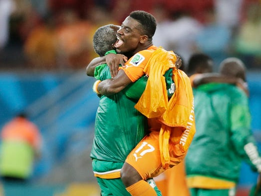 Ivory Coast's Serge Aurier is hugged by a team member after their 2-1 victory over Japan in a group C World Cup soccer match at the Arena Pernambuco in Recife, Brazil, Sunday, June 15, 2014.
