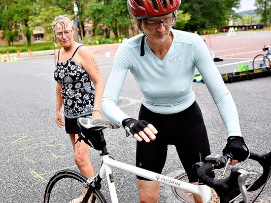 Nancy Williams-Smith, left, of York, looks on as teammate Leslie Bentz, right, also of York, prepares to take off on the 15-mile bike ride leg of the 2015 Y-TriDu5K at York College Grumbacher Sports Center.