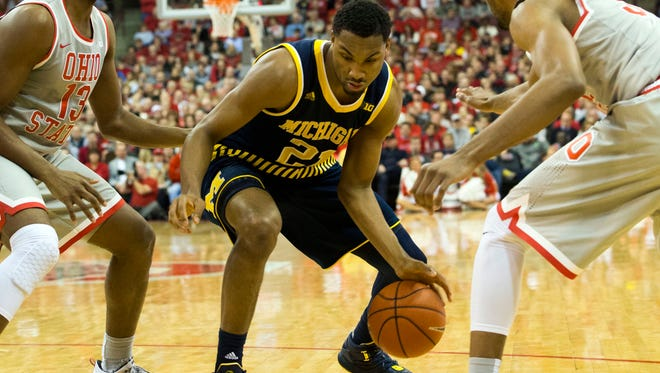 Michigan Wolverines guard Zak Irvin (21) cuts between Ohio State Buckeyes guard JaQuan Lyle (13) and center Trevor Thompson (32) at Value City Arena. Ohio State won the game 76-66.