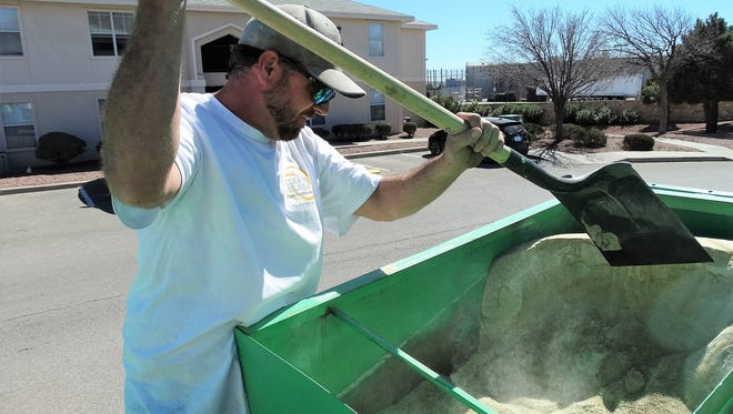Tony Miller, owner of Clean Blast, LLC, shovels glass sand in a hopper at this house, before he grinds it into even finer particles.