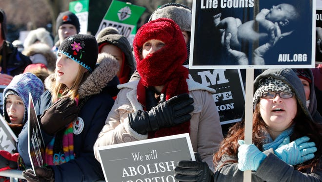 Demonstrators put their hands to their hearts as they recite the Pledge of Allegiance at the 2014 March for Life.