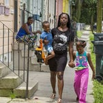 Shawanda Holmes, walks outside of her New Orleans home with her children Louis Lockett and Saniyah Holmes.