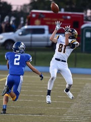 South Lyon's Brenden Lach (81) gets by Lakeland's Leo Skupin (2) to make the first-half catch.