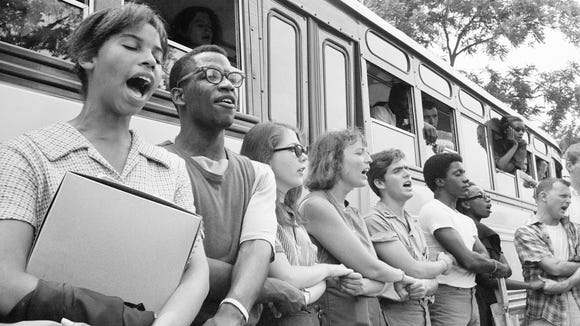 Student civil rights activists join hands and sing