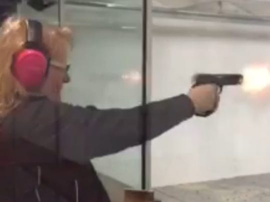 Jacqulyn Morrill practicing shooting her pistol at an indoor shooting range.