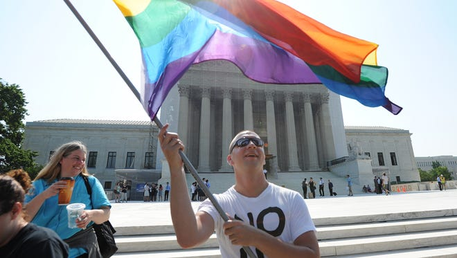 Vin Testa of Washington, D.C., waves a rainbow flag outside the U.S. Supreme Court on June 25, 2013. The Alabama Court of Criminal Appeals on Friday, June 13, 2014, said a state law criminalizing consensual homosexual conduct is unconstitutional.