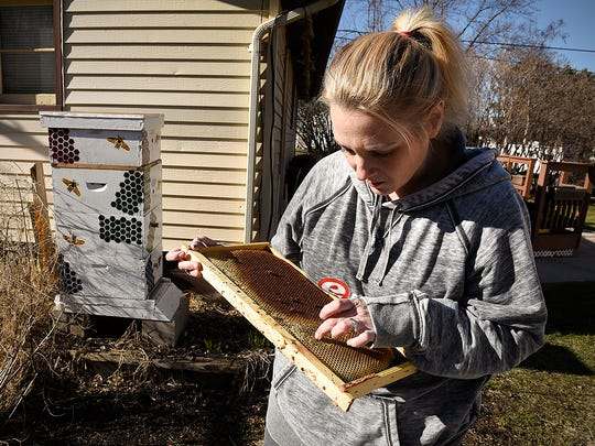 Leah Beack opens her bee hive Monday, April 11, to see how the bees did over the winter in Sauk Rapids. Beack's hives sit next to her garage and garden, out of sight.