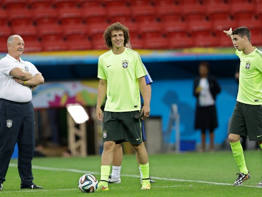 Brazil's David Luiz, center, coach Luiz Felipe Scolari, left, and Oscar practice during an official training session the day before the group A World Cup soccer match between Brazil and Cameroon at the Estadio Nacional in Sunday, June 22, 2014. The hosts need at least a draw to advance to the second round, and a win will likely secure first place. Cameroon is already eliminated after losing its first two matches. (AP Photo/Andre Penner)