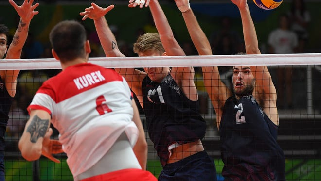Poland opposite spiker Bartosz Kurek (6) hits a shot against United States middle blocker Maxwell Holt (17) and wing spiker Aaron Russell (2) in a men's quarterfinal volleyball match at Maracanazinho during the Rio 2016 Summer Olympic Games.