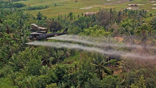 A U.S. Army Huey helicopter sprays Agent Orange during the Vietnam War.